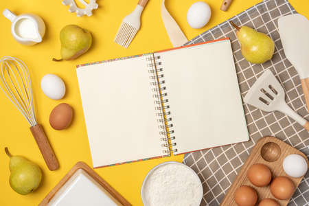 Open blank notebook, baking ingredients and cooking utensil, on yellow backgroun. Template for cooking recipes or your design. Top view Flat lay Mockup.