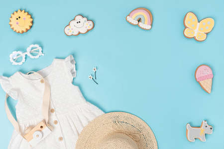 Stylish summer set of child clothes. White dress, the straw hat, sunglasses and funny gingerbread on blue background. Fashion girl lookbook concept. Top view Flat lay Copy space.