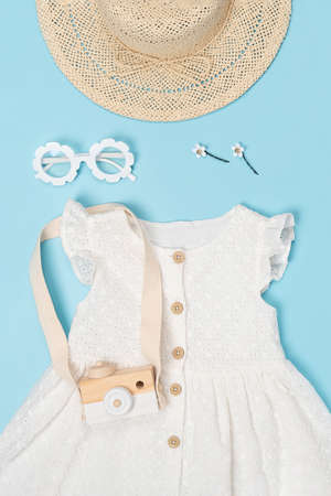Stylish summer set of child clothes. White dress, the straw hat, sunglasses and accessories on blue background. Fashion girl lookbook concept. Top view Flat lay.