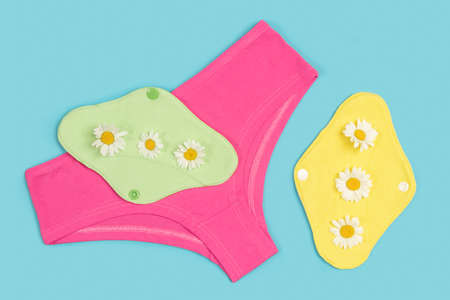 Bright panties and bamboo charcoal washable sanitary napkins with chamomile flowers on blue background. Healthy women's sanitary pads, reusable menstrual pads. Health care concept.