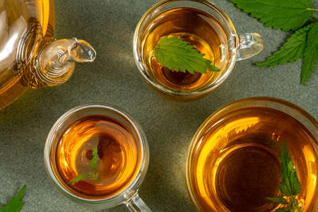 Cups of herbal tea, transparent teapot and nettle leaves on green background. Calming drink concept. Top view Flat lay. Stock fotó
