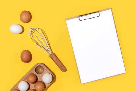 Eggs in wooden egg box, whisk and clipboard with white paper on yellow background. Flat lay Top view Mockup.