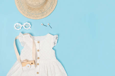Stylish summer set of child clothes. White dress, the straw hat, sunglasses and accessories on blue background. Fashion girl lookbook concept. Top view Copy space Flat lay. Stock fotó