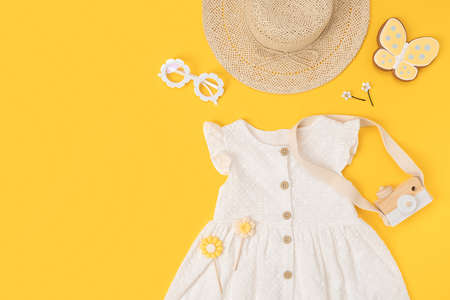 Stylish summer set of child clothes. White dress, the straw hat, sunglasses and accessories on yellow background. Fashion girl lookbook concept. Top view Copy space Flat lay. Stock fotó