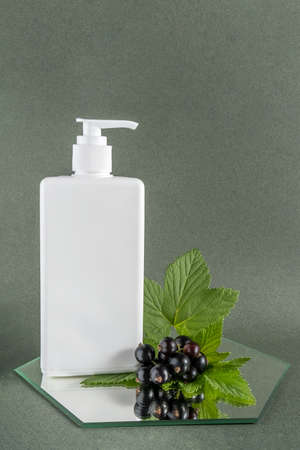 White cosmetic blank bottle with dispenser and sprig of black currant on mirror, green background. Natural Organic Beauty Cosmetic concept. Front view.