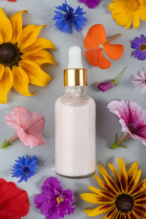 Pink anti-aging collagen, facial serum or other cosmetic product in glass bottle among the colored flowers on gray background. Natural Organic Spa Cosmetic concept Mockup Top view.