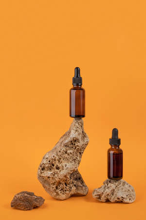 Serum or essential oil in brown glass dropper bottle on stones, orange background. Natural Organic Spa Cosmetic concept Front view.