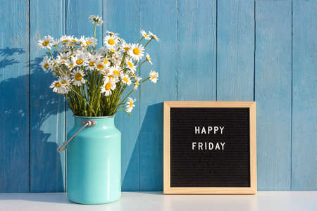 Happy Friday words on black letter board and bouquet of chamomile flowers on table against blue wooden wall. Concept Hello Friday. Stock fotó
