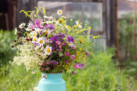 Bouquet of bright wild flowers in tin can vase on table outdoors, rural scene. Template for postcard. Concept Womens day, Mothers Day, Hello summer or Hello spring.