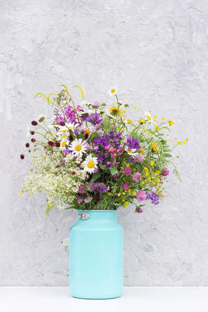 Bouquet of bright wild flowers in tin can vase on background gray stone wall. Template for postcard. Concept Women's day, Mothers Day, Hello summer or Hello spring.