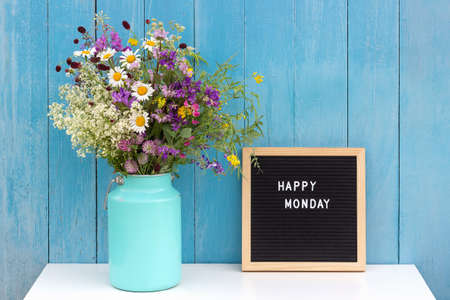 Happy Monday words on black letter board and bouquet of bright wild flowers in tin can vase on table against blue wooden wall. Concept Hello Monday.