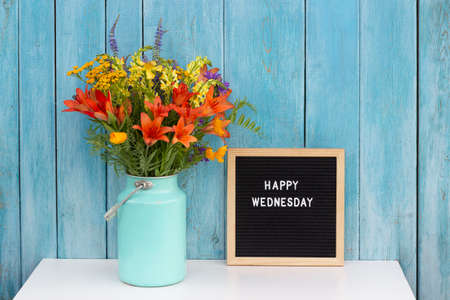 Happy Wednesday words on black letter board and bouquet of bright wildflowers in tin can vase on table against blue wooden wall. Concept Hello Wednesday. Stock fotó