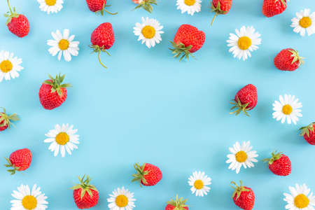Bright summer frame made with natural chamomile flowers and strawberry on blue background with copy space for your design. Top view Flat lay. Stock fotó