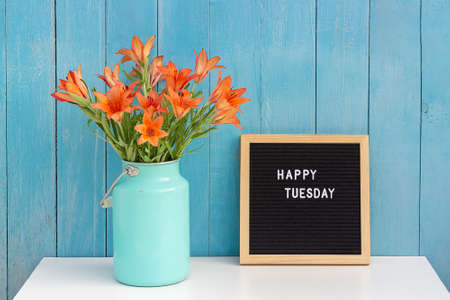 Happy Tuesday words on black letter board and bouquet of orange flowers on table against blue wooden wall. Concept Hello Tuesday.