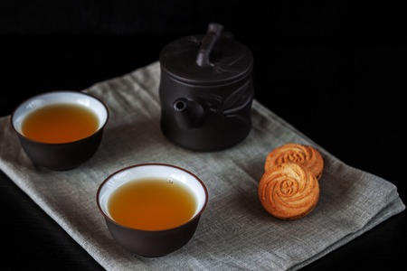 Chinese brown teapot and cups on a black wooden table 版權商用圖片