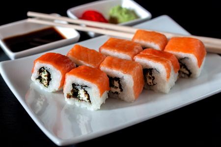 Philadelphia Sushi Roll made of Fresh Salmon, Avocado and Cream Cheese with black rice with cuttlefish ink inside. Traditional Japanese cuisine. Asian food