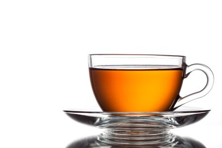 Cup of black tea and spoon, isolated on white