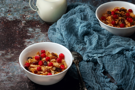 Two bowls of cornflakes on a dark gray background