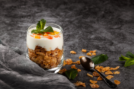 Cottage cheese dessert with cornflakes in a glass tumbler on a dark gray background 写真素材