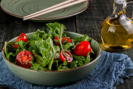 summer salad with tomatoes in green plate on wood table 免版税图像
