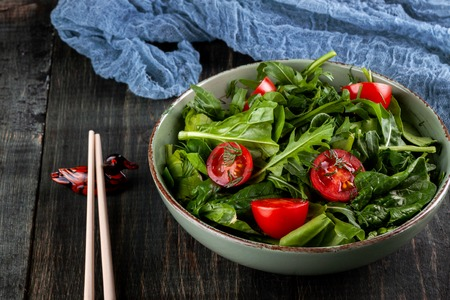 summer salad with tomatoes in green plate on wood table Imagens