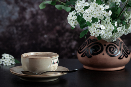 Close-up of a cup of coffee and a branch of blooming spirea in a ceramic vase on a dark background