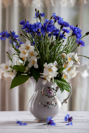Vase with spring wildflowers on the table 写真素材
