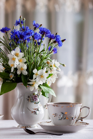 A cup of tea on the table with a bouquet of the first spring flowers. Healthy lifestyle