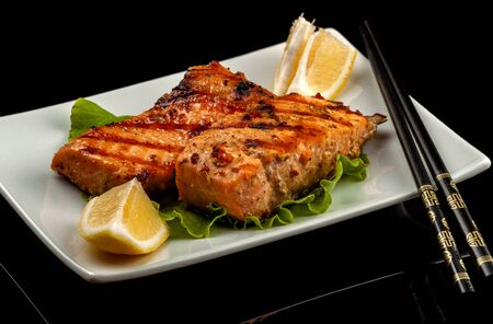 Fish, trout, chum salmon, humpback, a piece baked, grilled, with a slice of lemon and lettuce