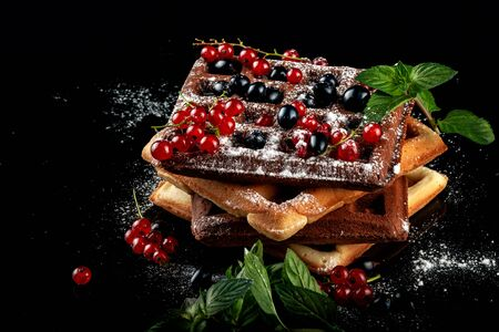 Freshly baked Viennese waffles lie on a black table. Banque d'images
