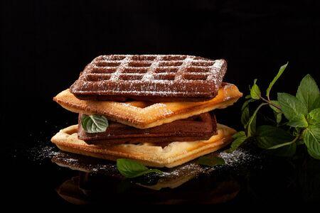 Freshly baked Viennese waffles lie on a black table. Reklamní fotografie