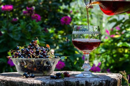 On an old wooden table there is a wine in a decanter, a glass and a glass vase with fresh currants