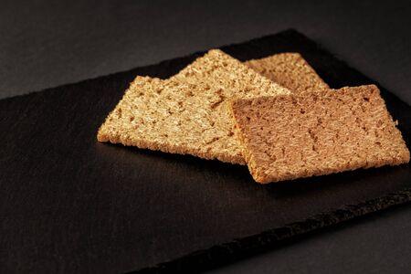 Crispy rye bread on a serving board with rye ears