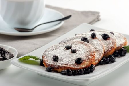 A Cup of coffee with milk and a plate with a pancakes is on the table.
