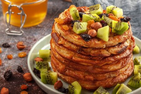 Pancakes with honey, kiwi, nuts and raisins are on the table