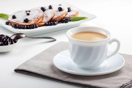 Cup of coffee with milk and a plate with pancakes on a white table.
