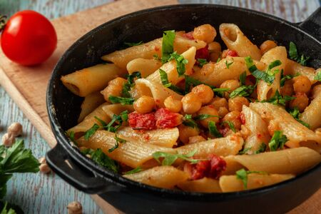Pâtes italiennes aux pois chiches, épices et tomates dans une casserole de portion