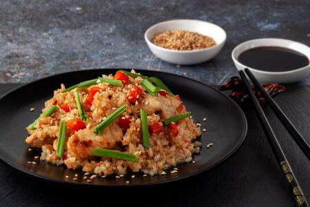 On a serving board, tori chahan fried Japanese rice with vegetables and chicken in soy sauce in a black plate