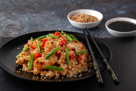 On a serving board, tori chahan fried Japanese rice with vegetables and chicken in soy sauce in a black plate 版權商用圖片