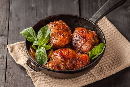 On a wooden table, chicken thighs and basil in a black cast-iron skillet