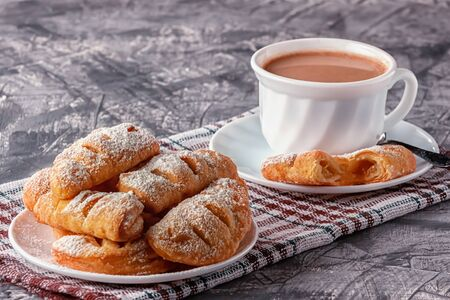 On a gray background, freshly baked homemade puffs with aromatic coffee