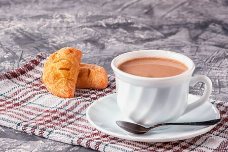 On a gray background coffee with cream and freshly baked puffs Фото со стока