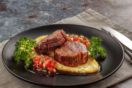 On a dish beef medallions with tomato salsa and cream polenta