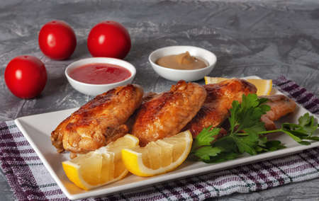 Freshly grilled chicken wings with tomatoes, lemons and parsley