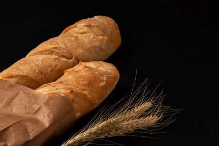 French baguettes in a paper bag and ears of wheat on a dark table top. view from above