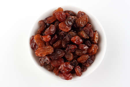 White bowl with raisins on a white background and space for text, top view.