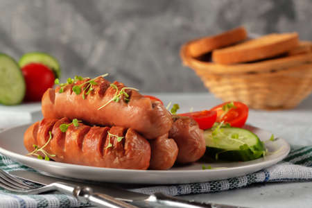 Grilled sausages with fresh vegetables are on the platter 版權商用圖片