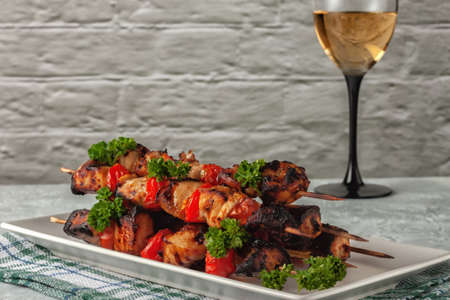 On a gray background chicken skewers with vegetables and a glass of white wine
