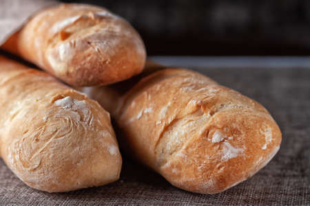 Freshly baked French baguettes on a table covered with cloth. Selective focus.
