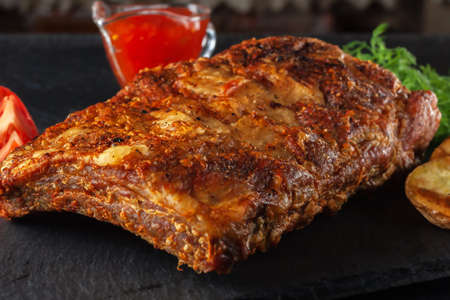 Grilled Spicy Ribs Served with Hot Chili Sauce and Fresh Tomatoes